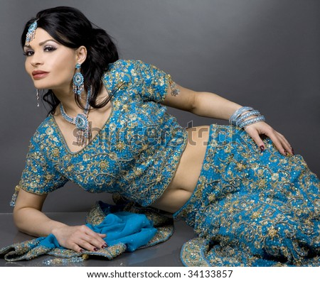 pretty brunette wearing traditional indian outfit on grey