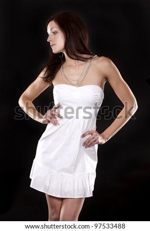 pretty brunette wearing white fashion dress on black background - stock photo
