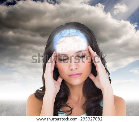 Pretty brunette with a headache against cloudy sky - stock photo