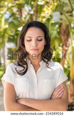 Pretty brunette with arms crossed on a sunny day