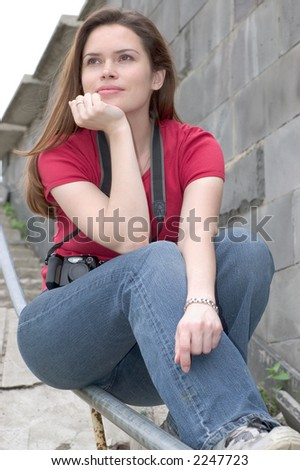 Pretty brunette with camera dreaming about something