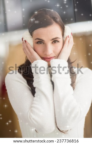 Pretty brunette with ear muffs against twinkling stars - stock photo