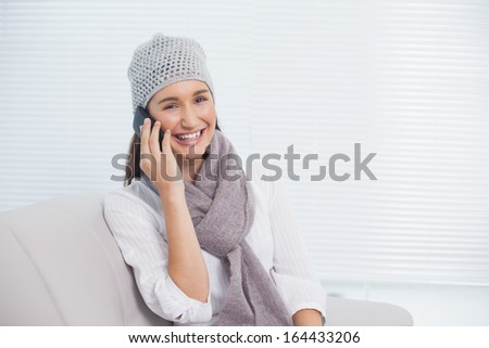 Pretty brunette with winter hat on having a phone call sitting on cosy sofa - stock photo