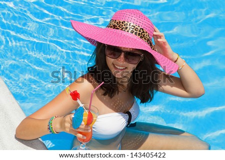 Pretty brunette woman in a hat enjoying cocktail in a swimming pool