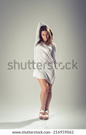 Pretty brunette woman in white dress posing in the studio - stock photo