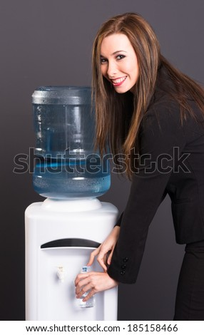 Pretty Brunette Woman Office Staff Water Cooler Workplace Drink - stock photo