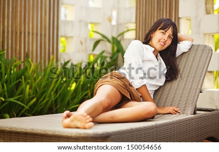 pretty brunette woman relaxing on a lounger outdoors - stock photo