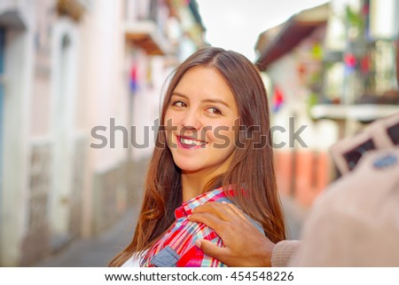 Pretty brunette woman turns around smiling while boyrfriends hand touches her shoulder, vibrant colors and blurry urban background