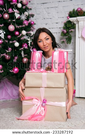 Pretty brunette woman wearing elegant white dress, sitting near a decorated Christmas tree and a fireplace, holding many presents, smiling, looking at camera.  - stock photo
