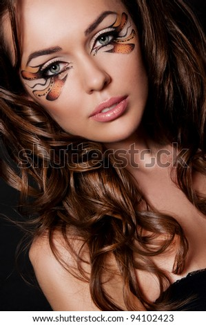pretty brunette woman with creative makeup on black background