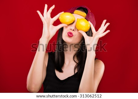 Pretty brunette woman, with dark hair, wearing on black shirt and claret cap, holding two lemons in front of her face, on the red background, in studio, waist up - stock photo