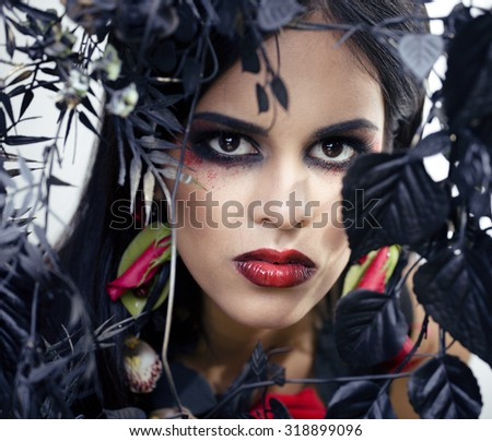 pretty brunette woman with rose jewelry, black and red, bright make up kike a vampire closeup red lips