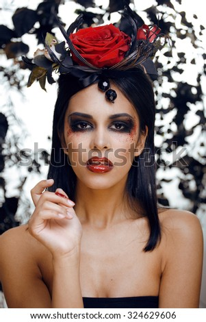 pretty brunette woman with rose jewelry, black and red, bright make up kike a vampire closeup red lips halloween - stock photo
