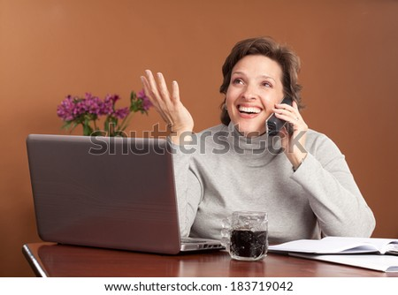 Pretty brunette working or shopping at a laptop on the kitchen table with a cup of coffee talking on the phone smiling and gesturing with her hand