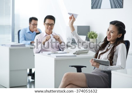 Pretty business lady launching paper plane when her colleagues working in office