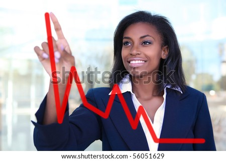Pretty business woman drawing a graph on a glass window at office - focus is on woman - stock photo