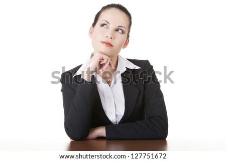 Pretty business woman in sitting at the desk and thinking, isolated on white - stock photo