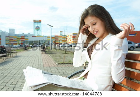 pretty business woman reading the newspaper - stock photo