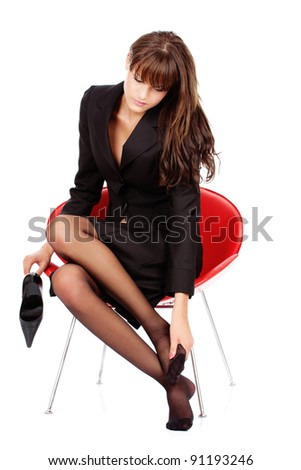 pretty business woman relaxing her feet with massage, isolated on white - stock photo