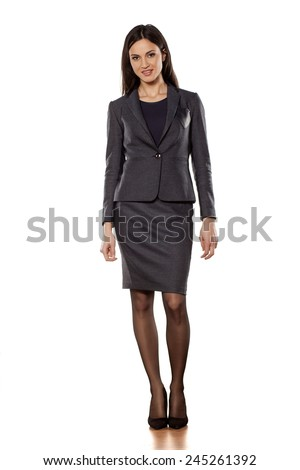 pretty business woman standing on white background - stock photo