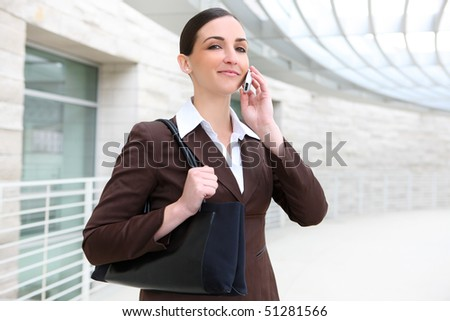 Pretty business woman talking on the phone and smiling at office building - stock photo