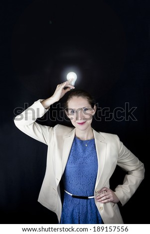 Pretty business woman wearing blue dress and yellow jacket holding a light bulb over her head