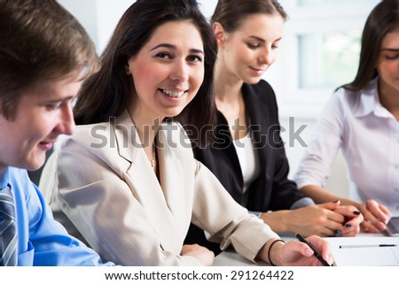 Pretty businesswoman at office with colleagues on the background