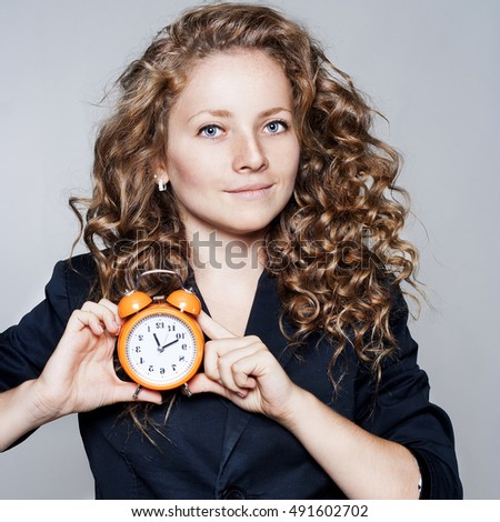 Pretty Businesswoman holding clock in hands. Deadline concept with woman holding alarm clock.