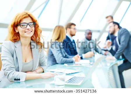 Pretty businesswoman in eyeglasses and suit looking at camera in working environment - stock photo