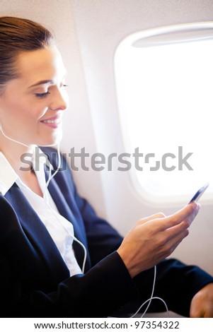 pretty businesswoman listening music on airplane - stock photo