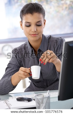 Pretty businesswoman sitting at desk in bright office, drinking coffee.