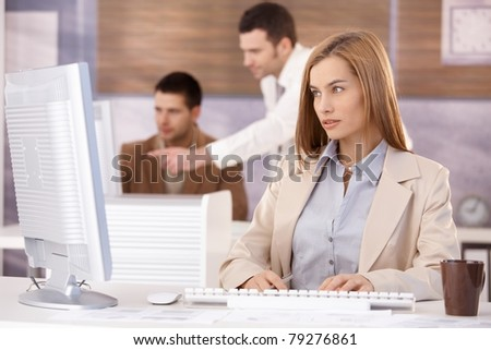 Pretty businesswoman sitting at desk, working on computer, team working in background.? - stock photo