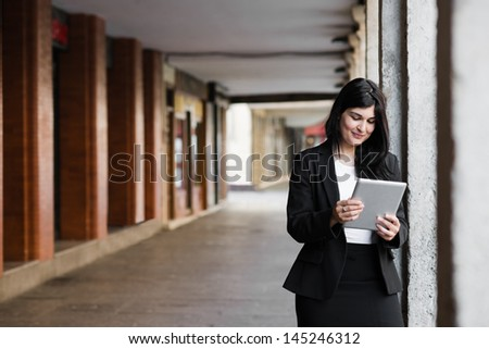 Pretty businesswoman surfing on the net in the street - stock photo