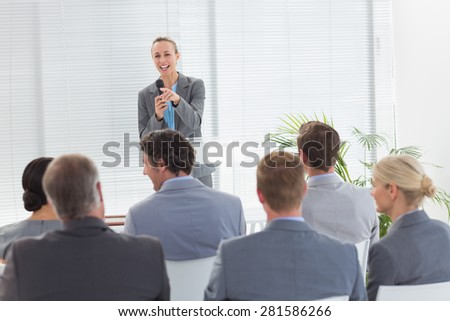 Pretty businesswoman talking in microphone during conference in meeting room - stock photo