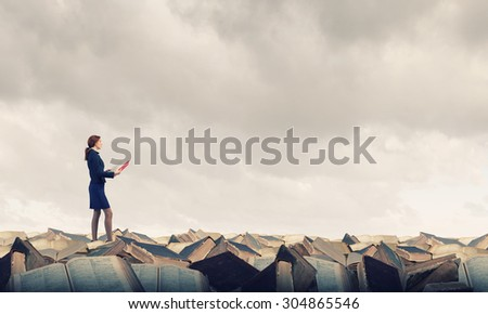 Pretty businesswoman walking on pile of old books - stock photo