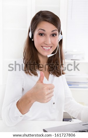 Pretty businesswoman with headset sitting at desk with giving thumbs up in white clothes - at the doctor - stock photo