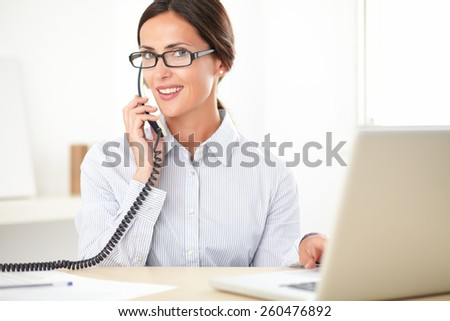 Pretty businesswoman with spectacles using the phone while smiling in the office - stock photo