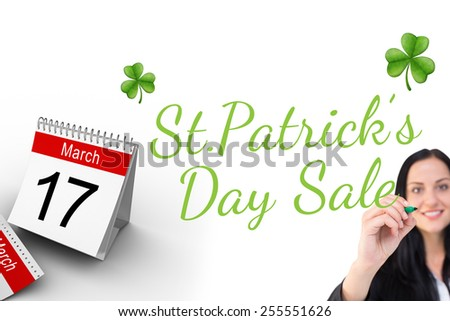 Pretty businesswoman writing with marker against shamrock - stock photo