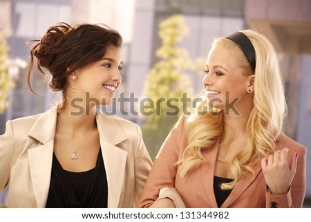Pretty businesswomen hugging, smiling happy outdoors. - stock photo