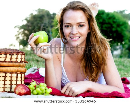 Pretty carefree summer girl having a picnic, lying on blanket holding a green apple - stock photo