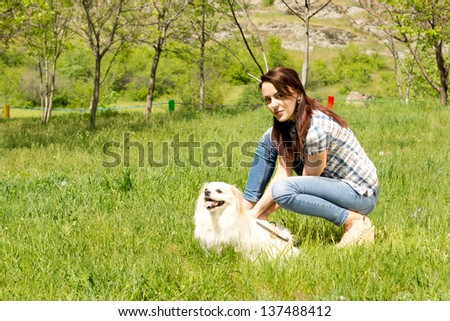 Pretty casual young woman in jeans bending down and playing with her cute little long haired dog in green grass in the countryside - stock photo