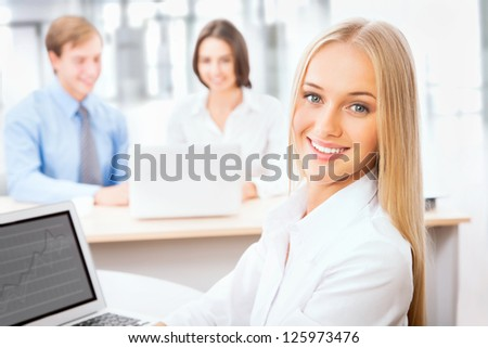 Pretty Caucasian business woman at office with colleagues on the background - stock photo