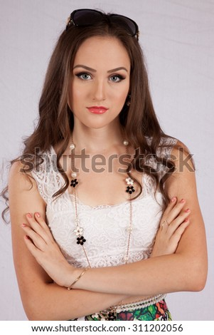 Pretty Caucasian girl looking thoughtful with sunglasses on the top of her head and her arms folded,