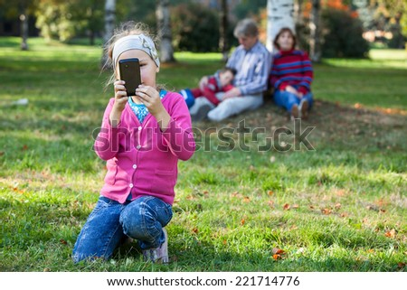 Pretty Caucasian girl making picture with phone, father, mother and brother are on background - stock photo