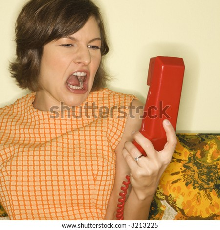 Pretty Caucasian mid-adult woman screaming at red telephone receiver. - stock photo