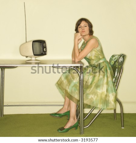 Pretty Caucasian mid-adult woman wearing green vintage dress sitting at 50's retro dinette in front of old televsion looking bored. - stock photo