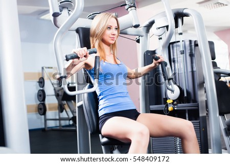 Pretty Caucasian smiling woman is working out on butterfly machine. Young Bodybuilder Doing Exercise For Chest In The Gym.