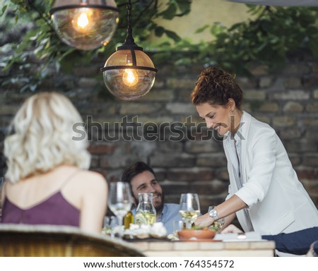 Pretty Caucasian smiling woman putting a plate with meal on dining table at backyard celebration.