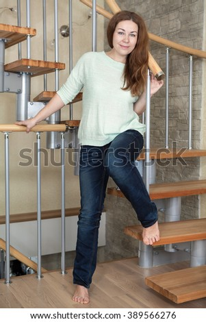 Pretty Caucasian woman dressed in jeans and with bare feet stands on domestic spiral staircase