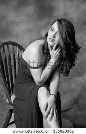 Pretty Caucasian woman in a sexy formal   dress,  looking at the camera with a flirting expression in black and white